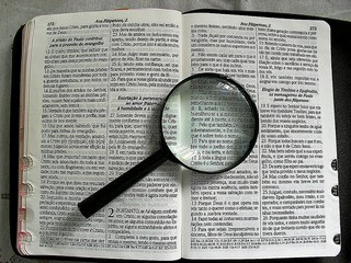 Bible open with magnifying glass on it.